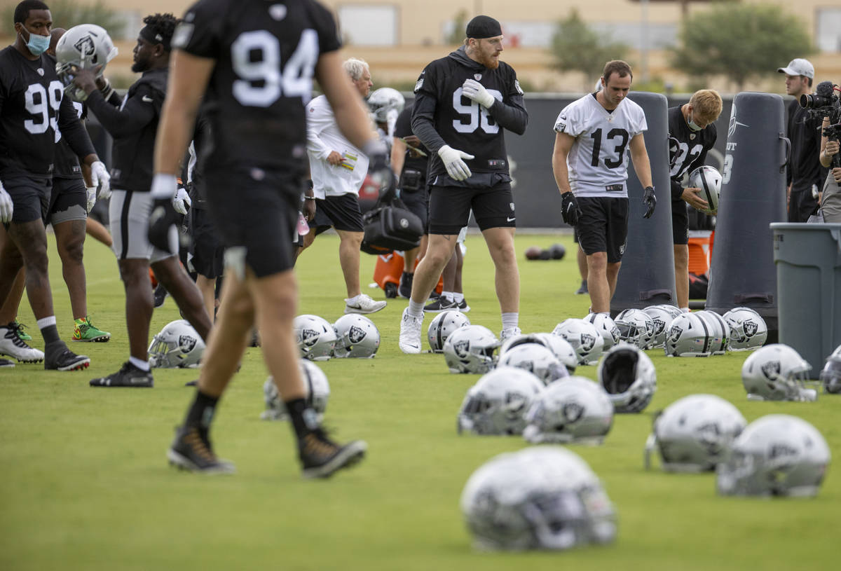 Raiders defensive end Maxx Crosby (98) and teammates head to their helmets during training camp ...