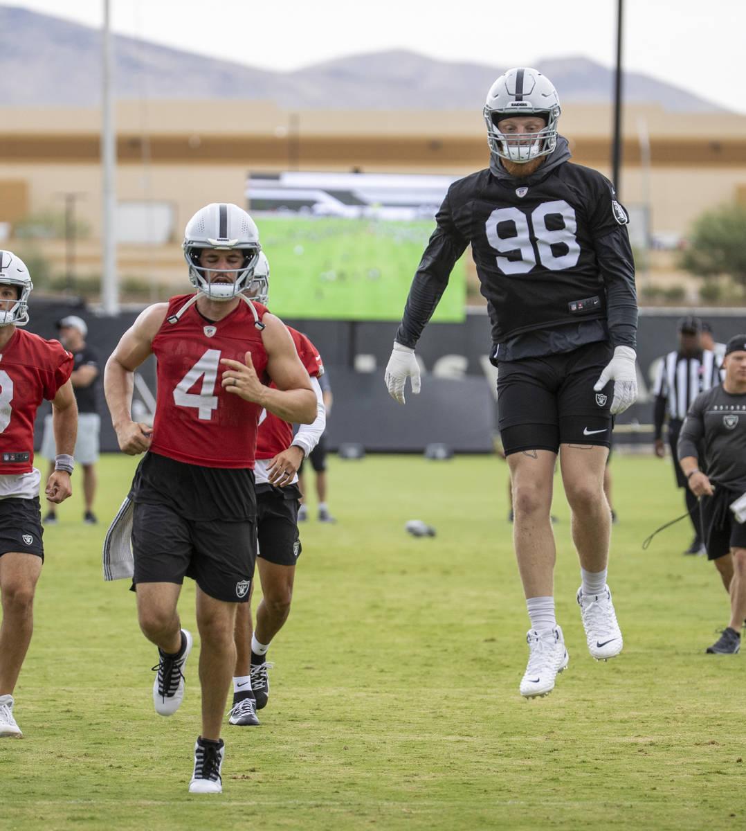 Raiders defensive end Maxx Crosby (98) leaps in the air as quarterback Derek Carr (4) runs alon ...