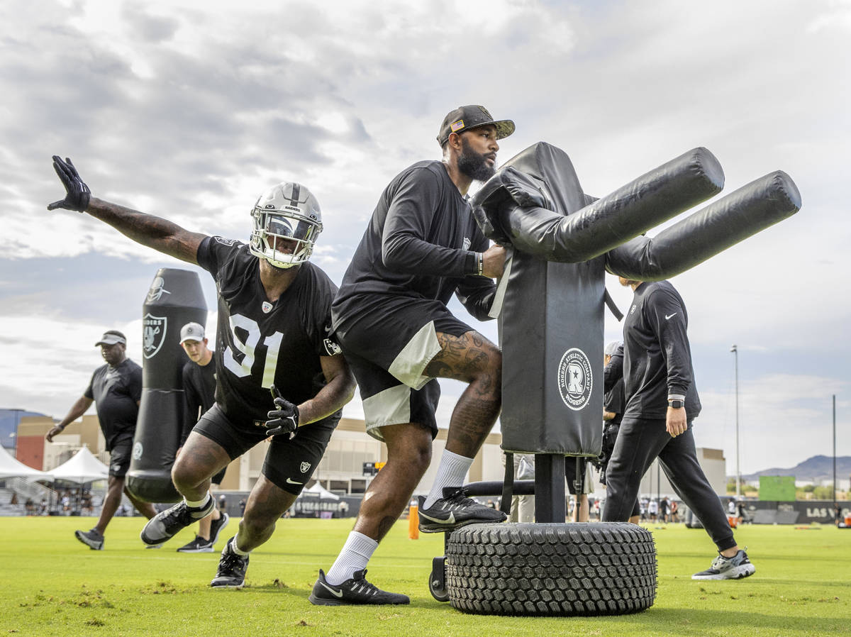 Raiders defensive end Yannick Ngakoue (91) curls around an obstacle during training camp at the ...