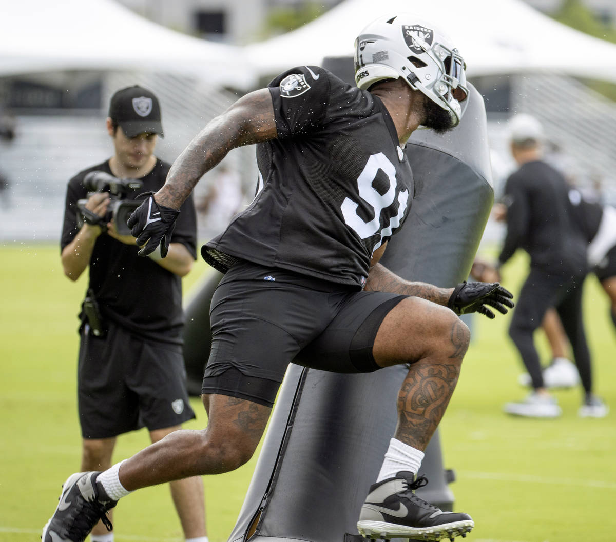 Raiders defensive end Yannick Ngakoue (91) runs around an obstacle during training camp at the ...