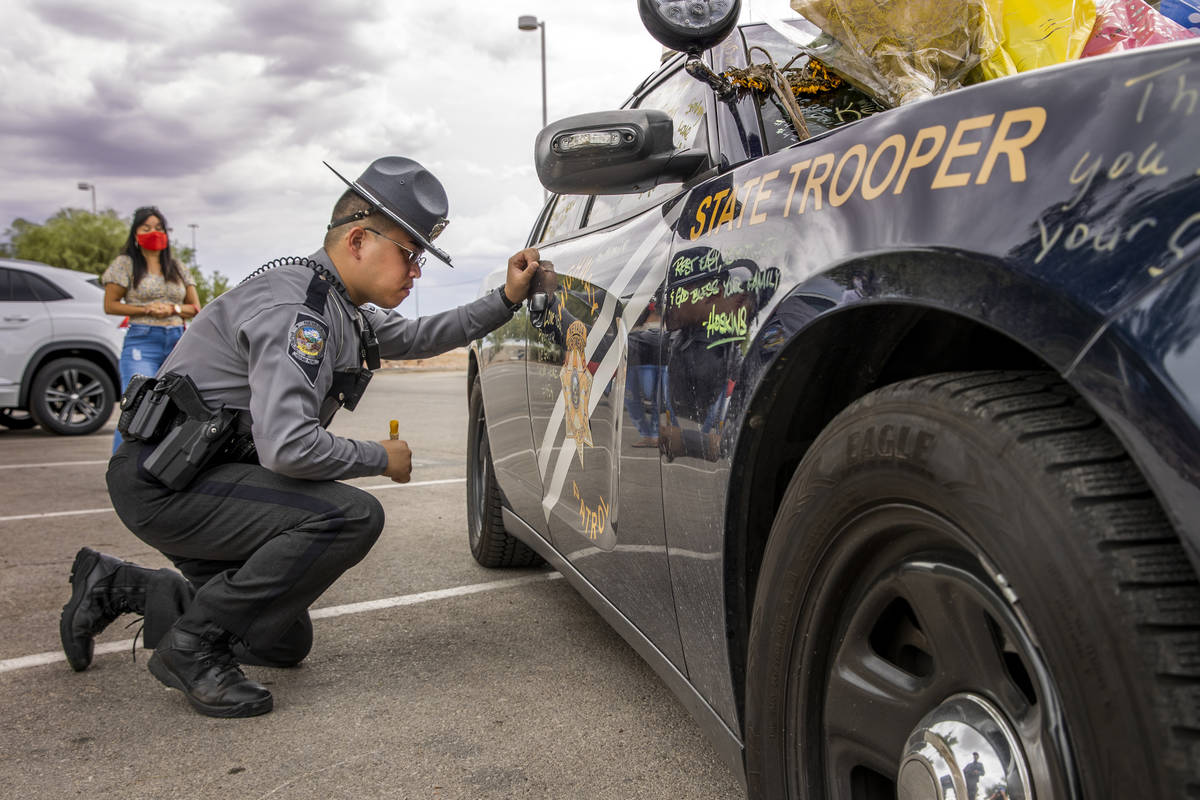 Nevada Highway Patrol Trooper Noah Villa takes a quiet moment after signing car #203 driven by ...