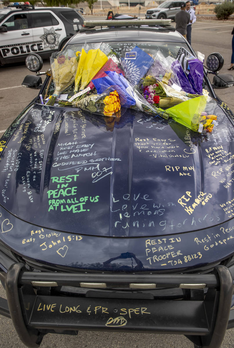 Car #203 driven by Nevada Highway Patrol Trooper Micah May is adorned with flowers and messages ...