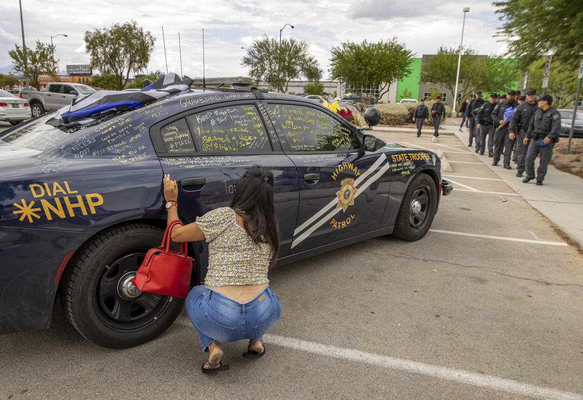 Well wishers are able to sign car #203 driven by Nevada Highway Patrol Trooper Micah May parked ...