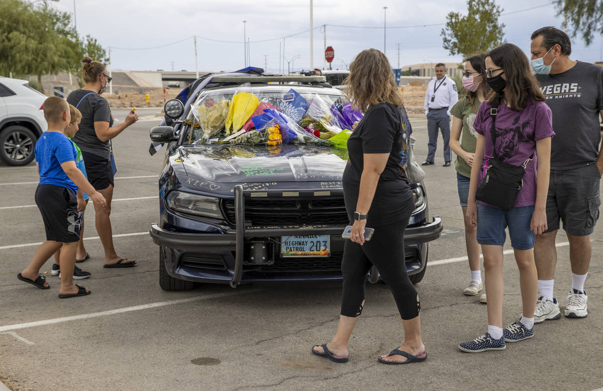 Well wishers arrive to view and sign car #203 driven by Nevada Highway Patrol Trooper Micah May ...
