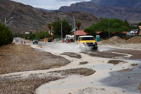 Vehicles travel down Craig Road, east of Fort Apache Road, among debris and receding flash floo ...