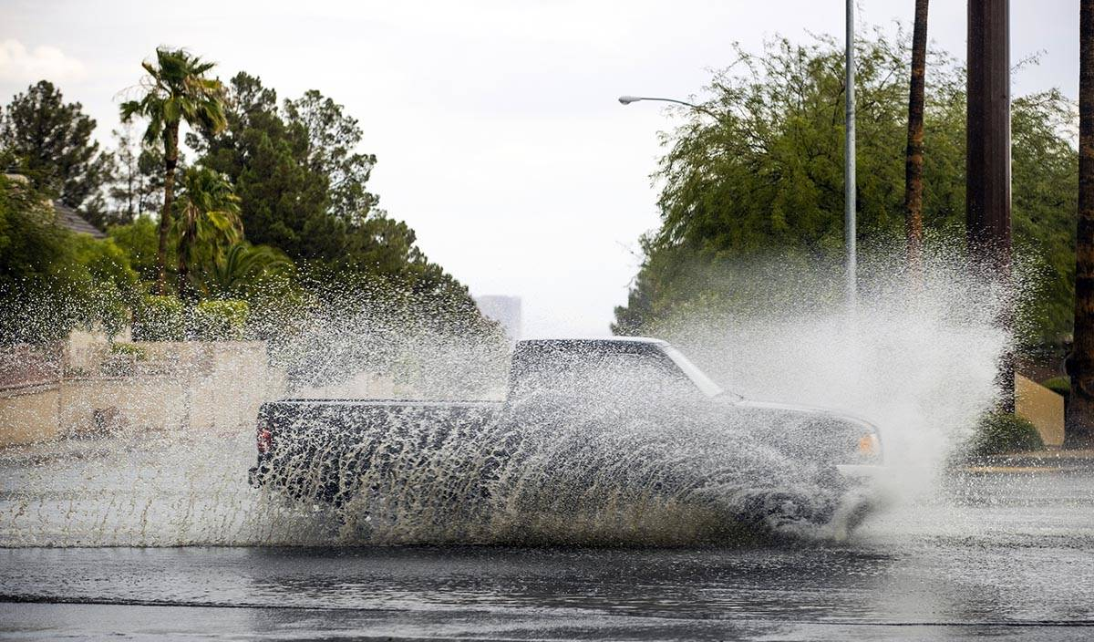 A truck drives through high water on South Buffalo Drive at West Darby Avenue as rain continues ...