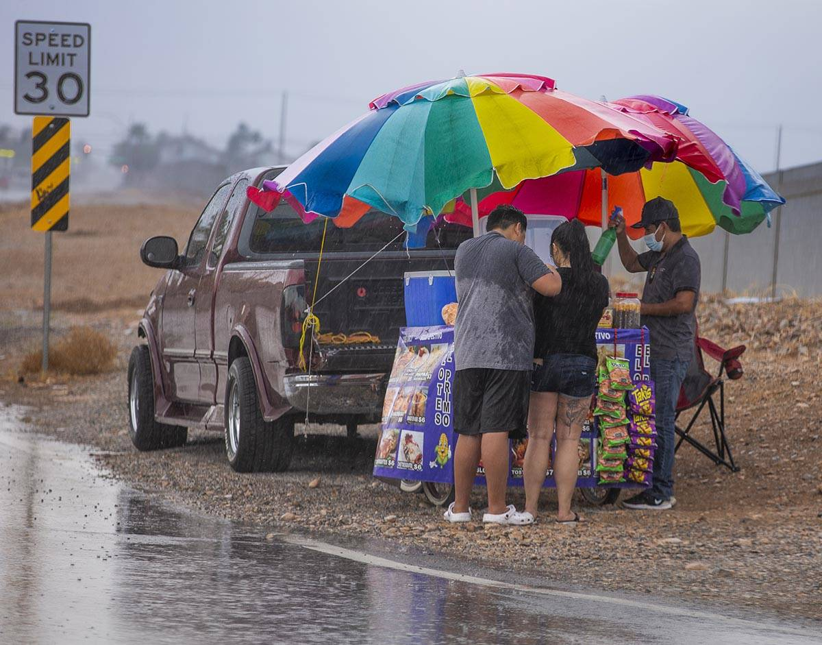 People stop for a bite to eat under some umbrellas of a cart vendor along West Twain Avenue as ...