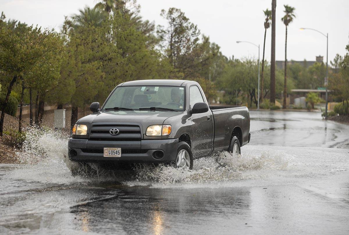 A truck navigates through high water about West Darby Avenue and South Blue Monaco Street as ra ...