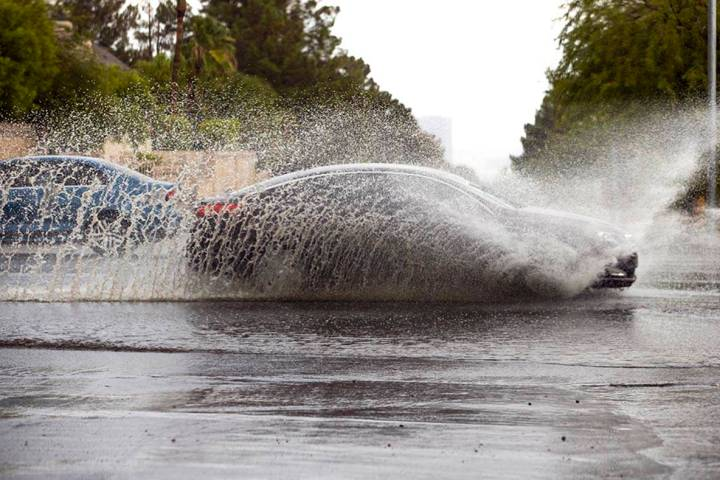 A car drives through high water on South Buffalo Drive at West Darby Avenue as rain continues a ...