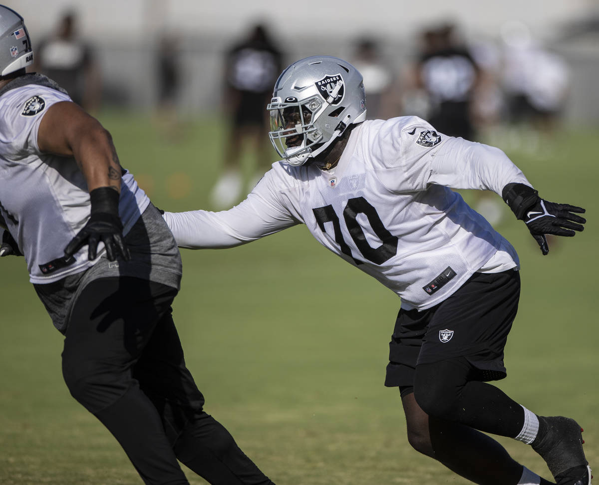 Raiders offensive tackle Alex Leatherwood (70) runs through drills during training camp on Satu ...