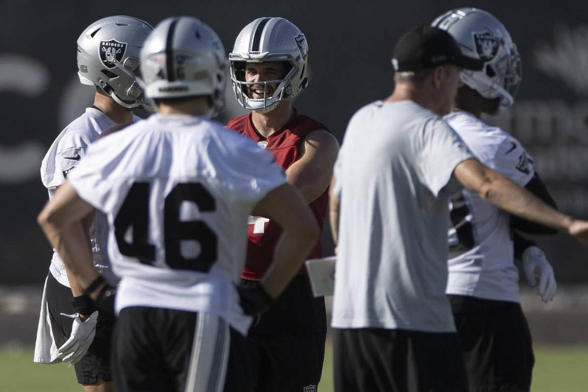 Raiders quarterback Derek Carr (4), red, directs the offense during training camp on Saturday, ...