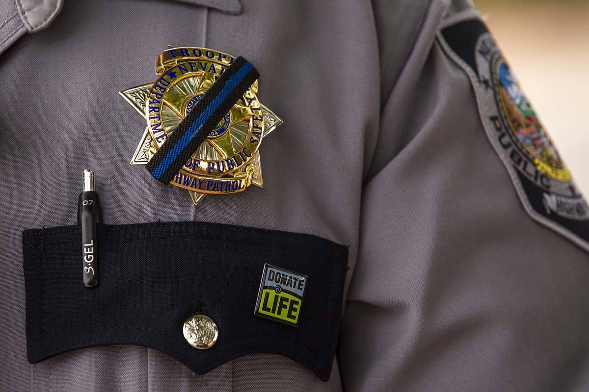 Nevada Highway Patrol Trooper Noah Villa wears a black band on his badge in remembrance of fell ...