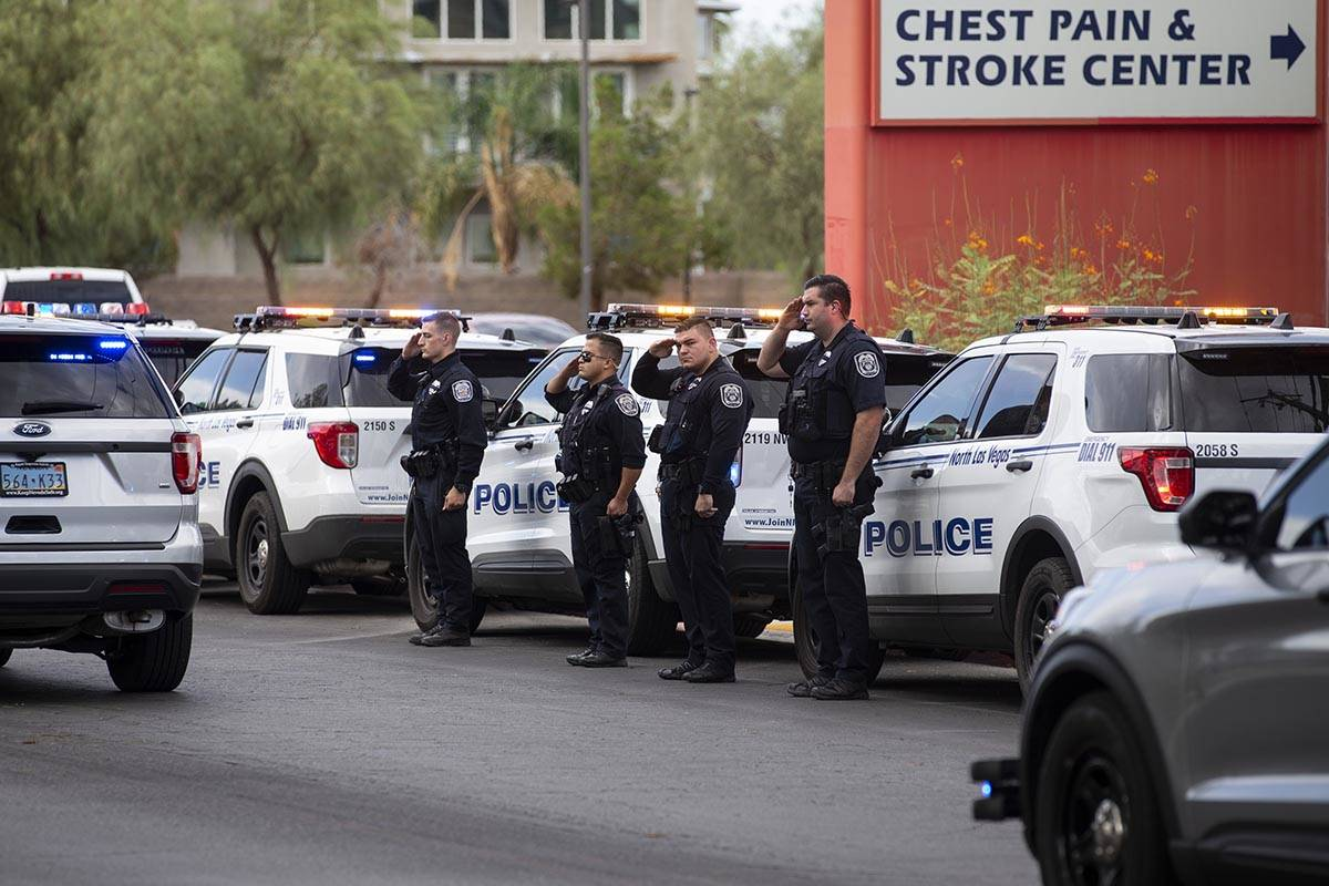 North Las Vegas police officers salute to a procession moving the body of slain Nevada Highway ...