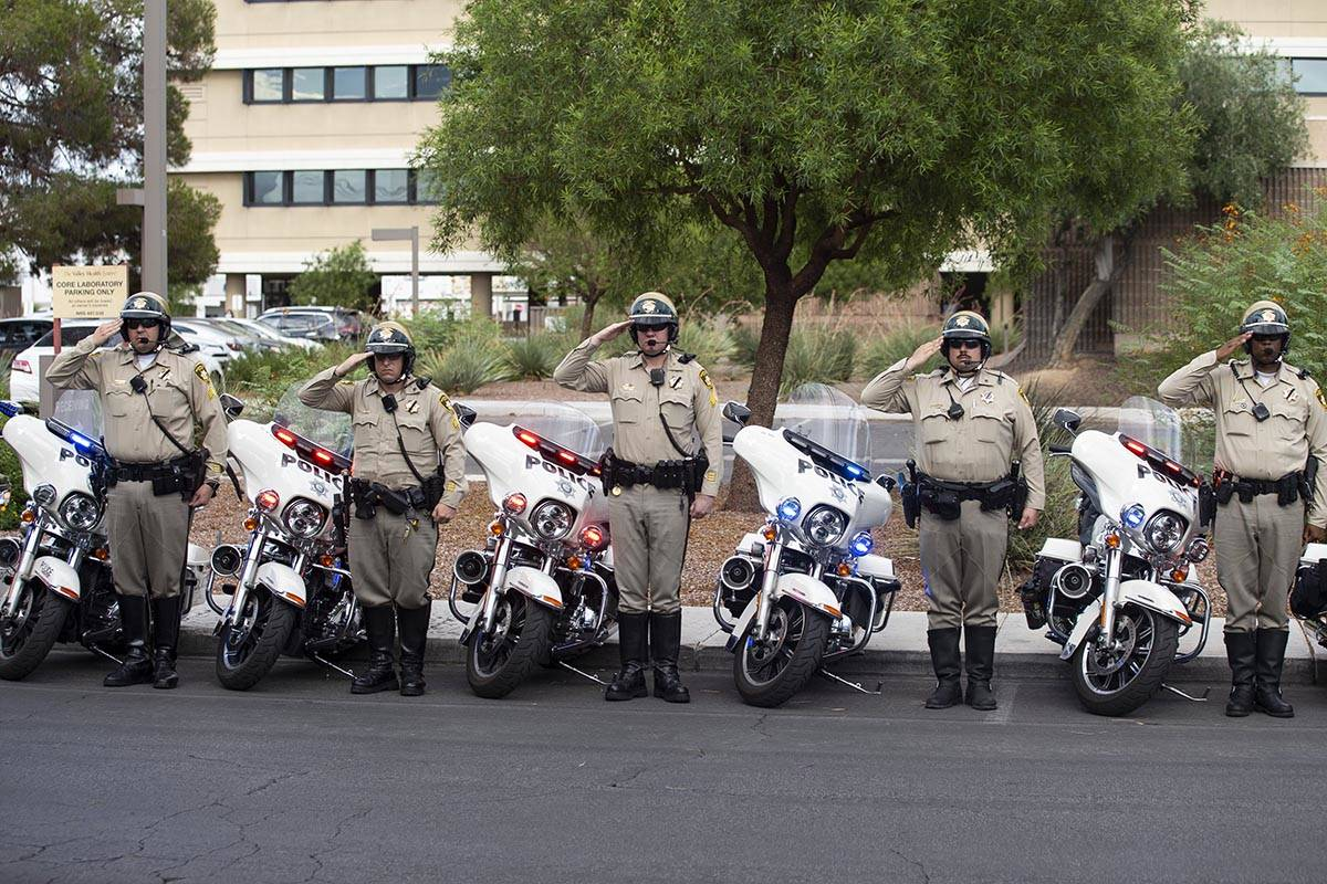Las Vegas police officers salute to a procession moving the body of slain Nevada Highway Patrol ...
