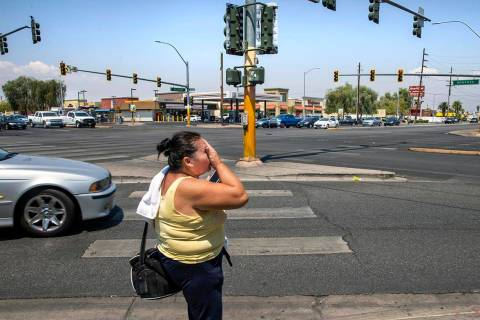 A woman wipes sweat from her face while walking at the intersection of North Eastern Avenue and ...