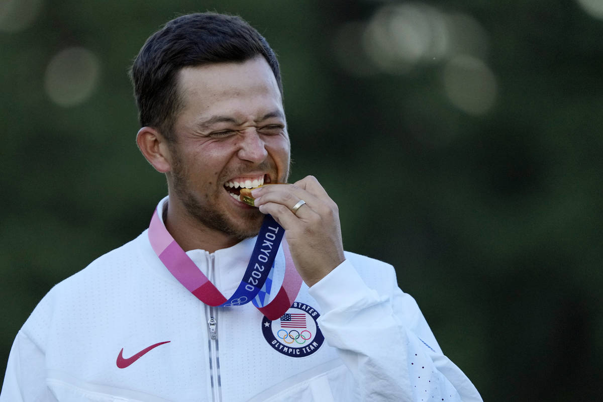 Xander Schauffele, of the United States, walks bites his gold medal in the men's golf at the 20 ...