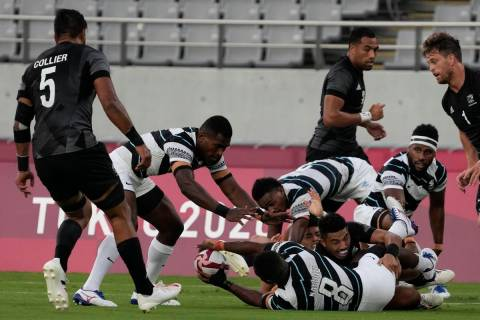 Fiji's Waisea Nacuqu passes off the ground to Aminiasi Tuimaba in their men's rugby sevens gold ...