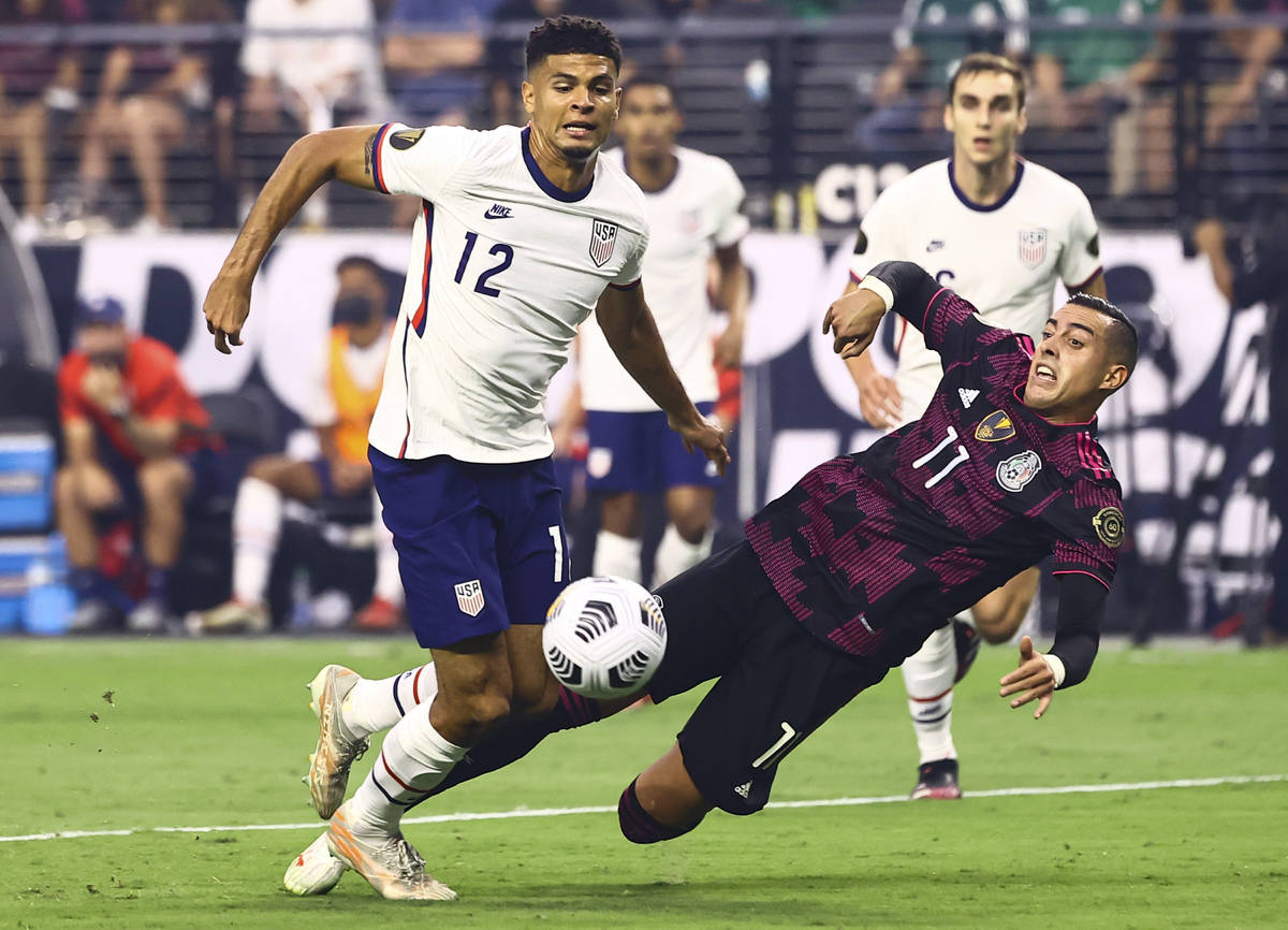 Mexico forward Rogelio Funes Mori (11) gets tripped up in front of United States defender Miles ...