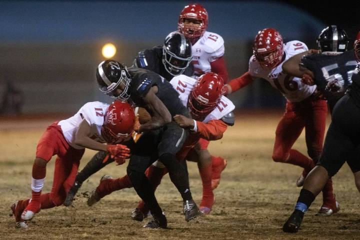 Desert Pines' running back Jovantae Barnes (22) pushes through a tackle from Arbor View's quart ...