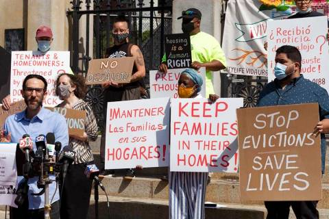 People from a coalition of housing justice groups hold signs protesting evictions during a news ...