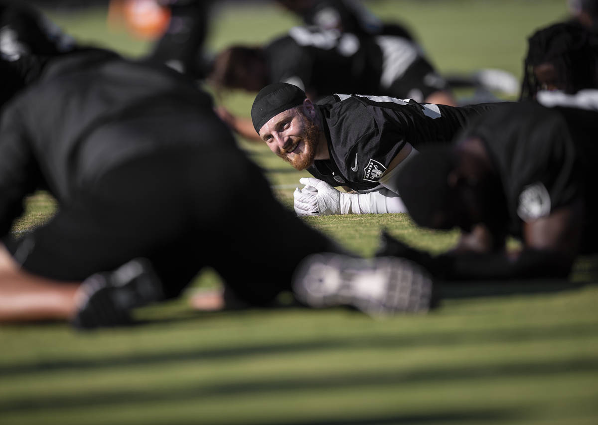 Raiders defensive end Maxx Crosby (98) stretches during training camp on Monday, Aug. 2, 2021, ...