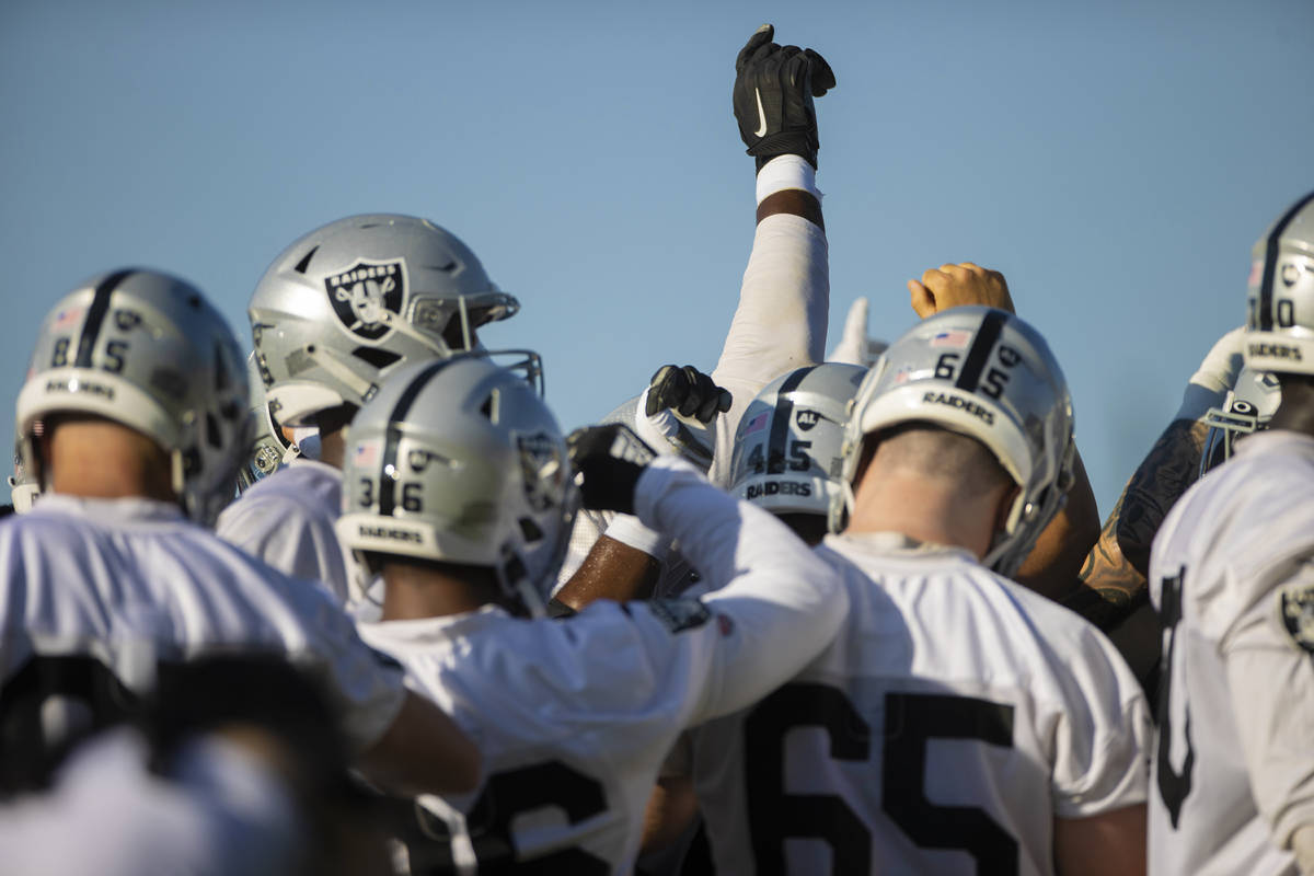 Raiders offensive players huddle before the start of training camp on Monday, Aug. 2, 2021, at ...