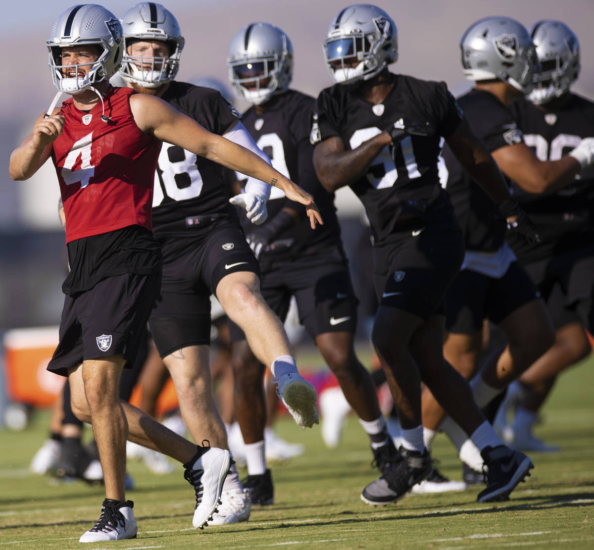 Raiders quarterback Derek Carr (4) warms up with teammates during training camp on Monday, Aug. ...