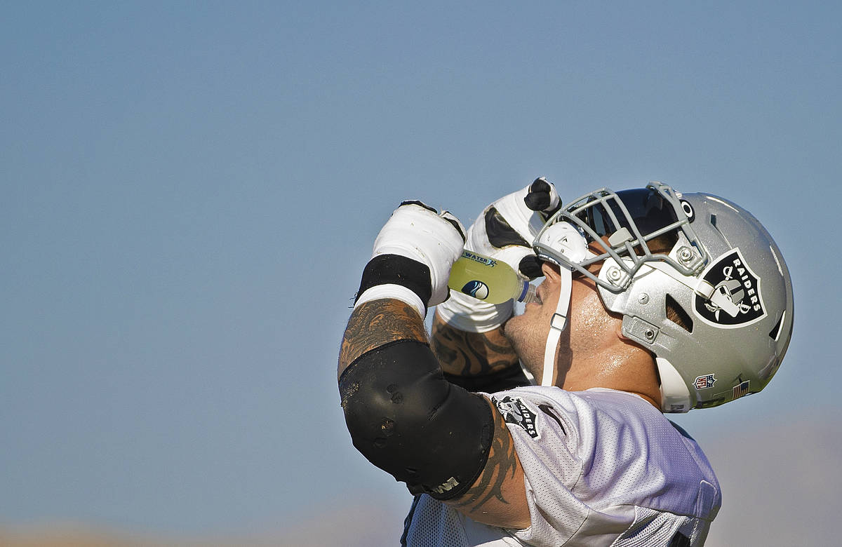Raiders offensive guard Richie Incognito (64) hydrates during a break at training camp on Monda ...