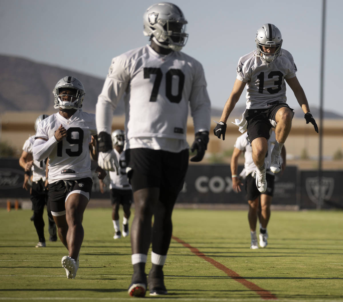 Raiders wide receiver Hunter Renfrow (13) leaps in the air while stretching at training camp on ...