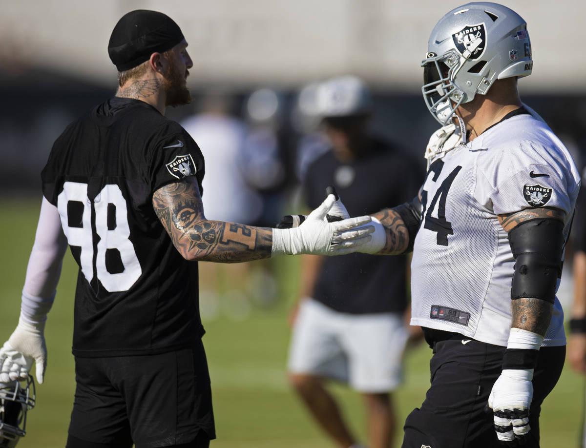 Raiders offensive guard Richie Incognito (64) and Raiders defensive end Maxx Crosby (98) greet ...