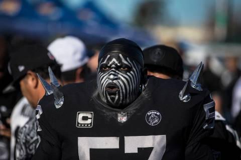 "Raiders super fan Wayne Mabry, known as ""Violator,"" walks through a tailgate outside ..."