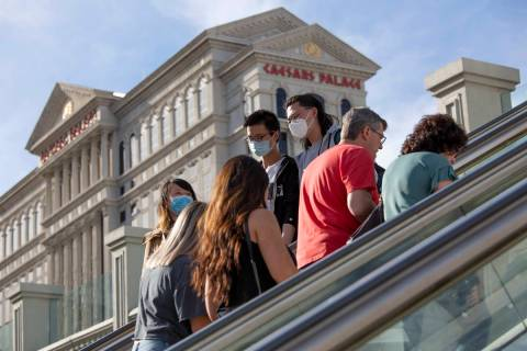 Visitors to the Las Vegas Strip ride escalators with Caesars Palace in the background on Friday ...