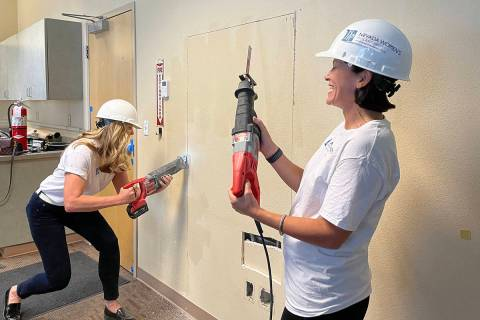 Members of the Nevada Women's Philanthropy cut into a wall at Bridge Counseling Associates, 422 ...