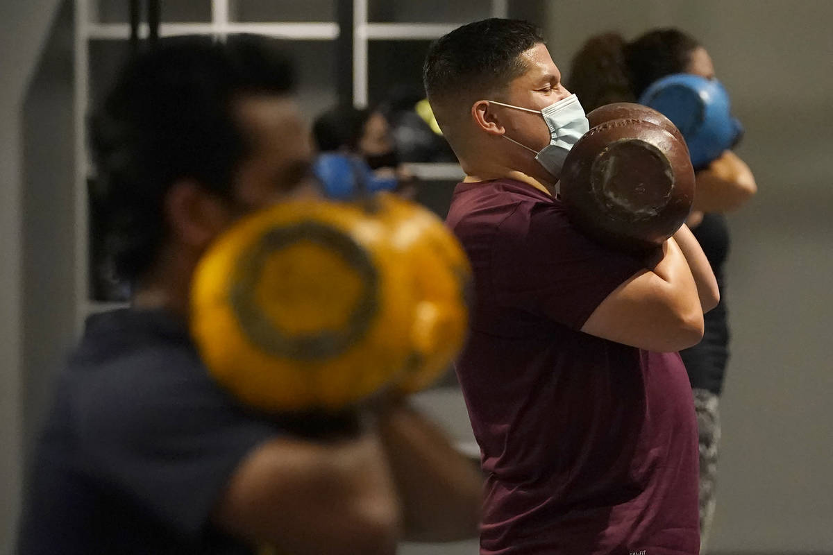 In this Nov. 24, 2020, file photo, Juan Avellan, center, and others wear masks while working ou ...