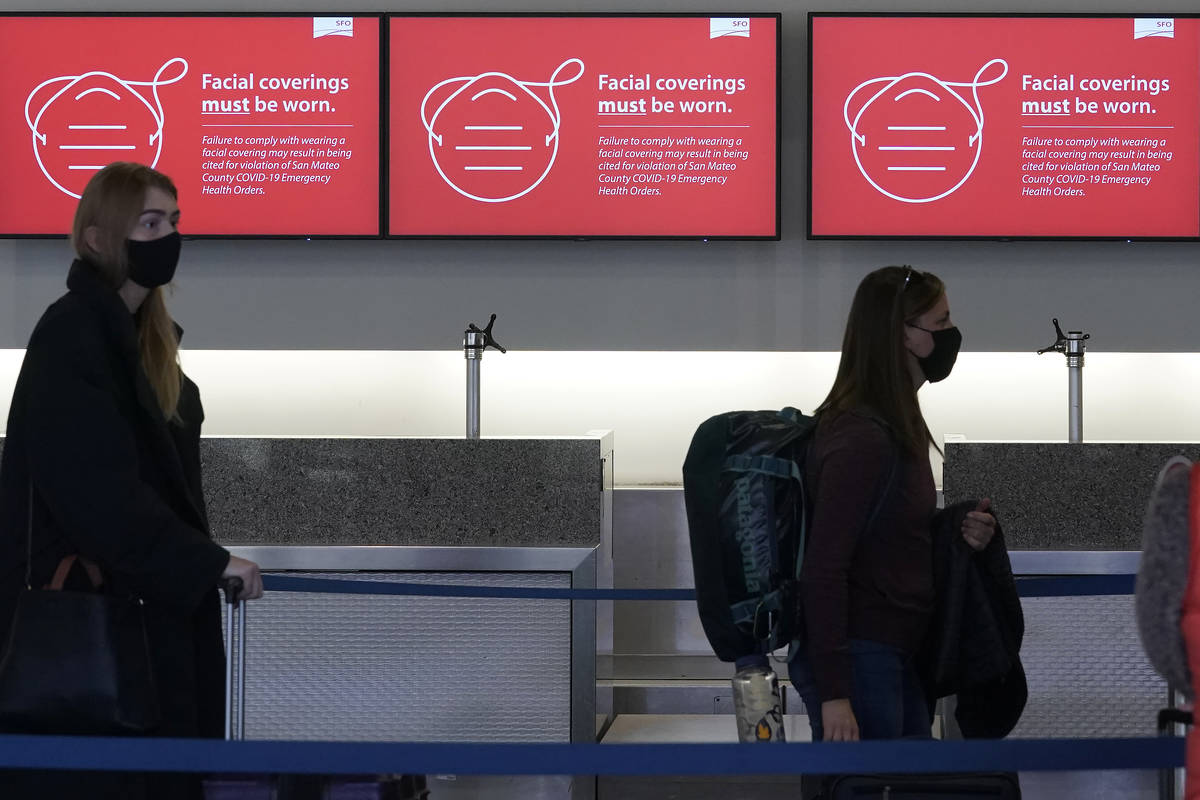 In this Dec. 22, 2020 file photo, signs advising facial covering requirements are shown as trav ...
