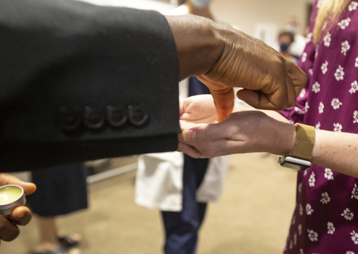 Father Don Ajoko, Phd. anoints the hands of healthcare workers and members of the nearly three ...