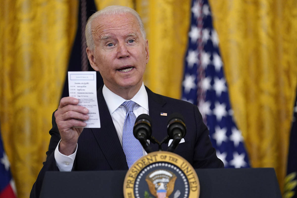 President Joe Biden holds a note card that has the number of COVID-19-related American deaths a ...