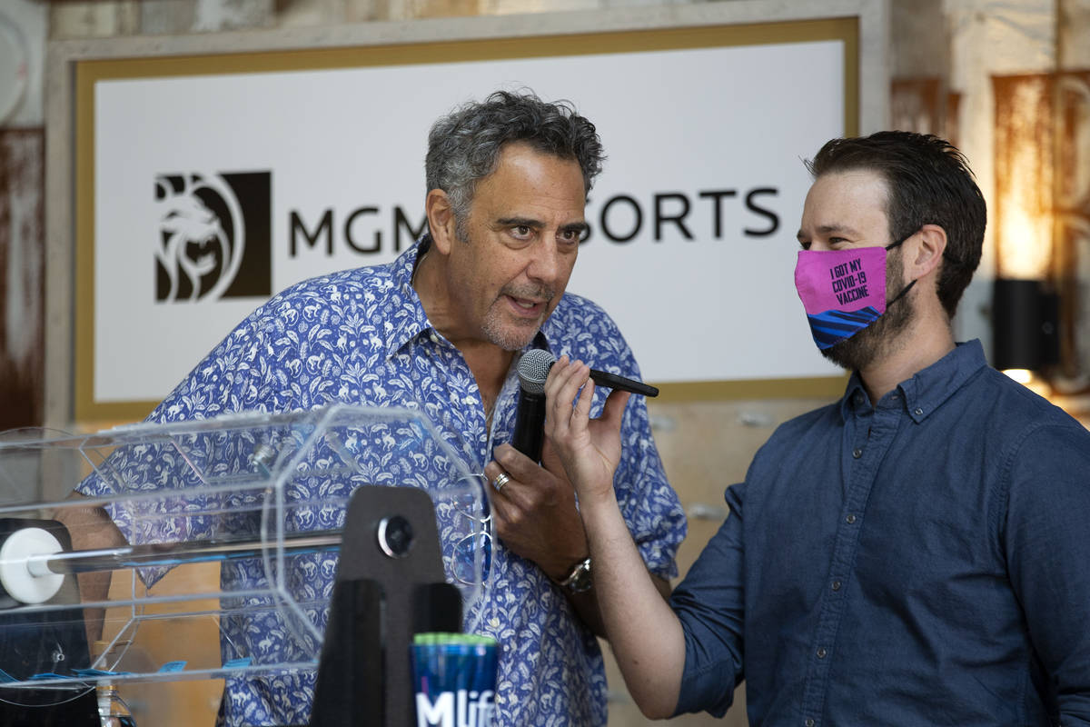 Comedian Brad Garrett, left, announces one of the raffle winners during a pop-up vaccination cl ...