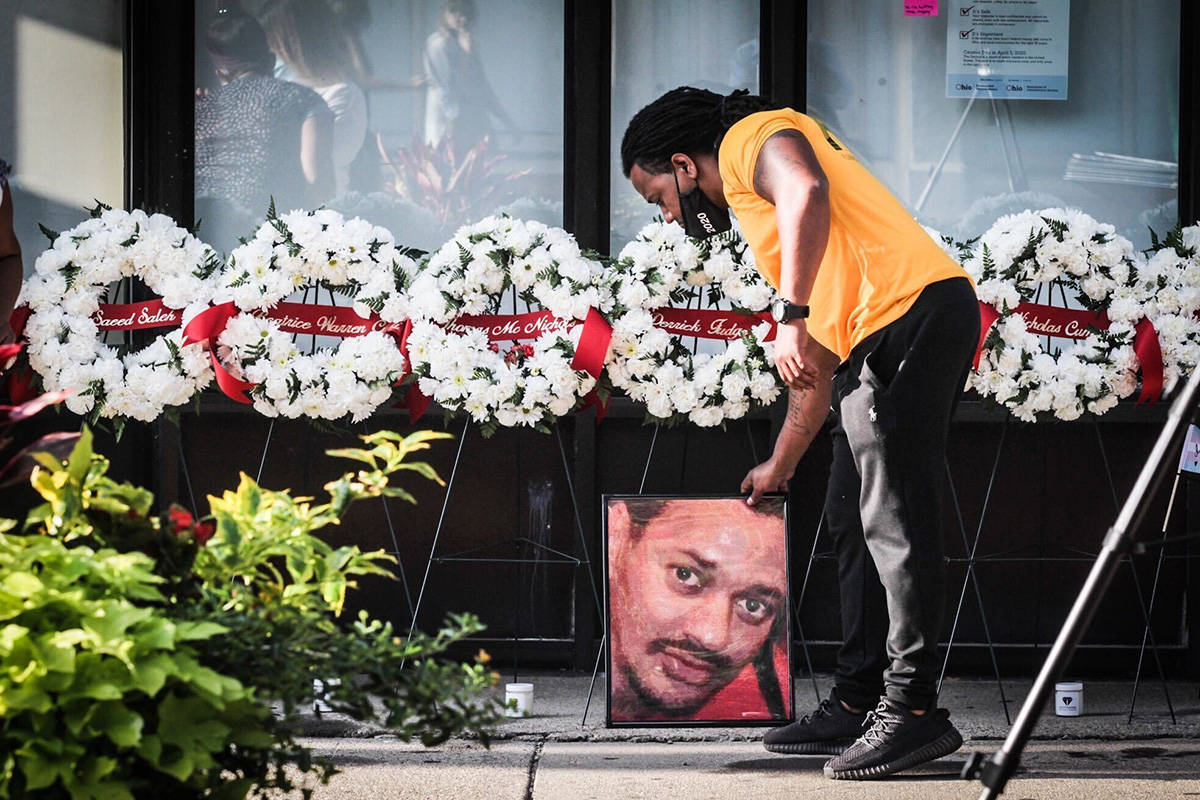 Dion Green places a portrait of his father, Derrick Fudge, of Springfield, Ohio, on Fifth Stree ...