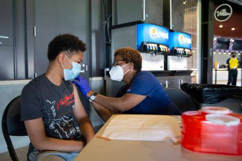 Joel Ferrell, 13, receives his first dose of the Pfizer COVID-19 vaccination from nurse Essie W ...