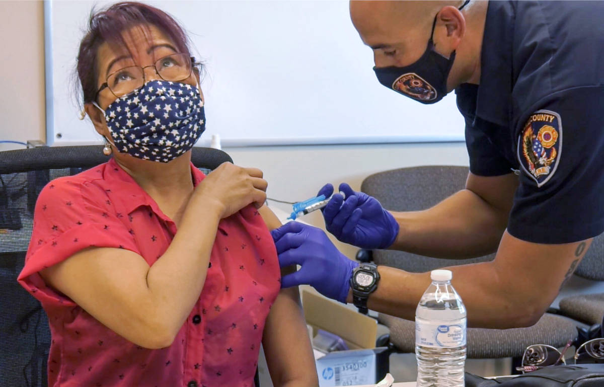 Grace Freckman receives a COVID-19 vaccine from Clark County Fire Department engineer and param ...