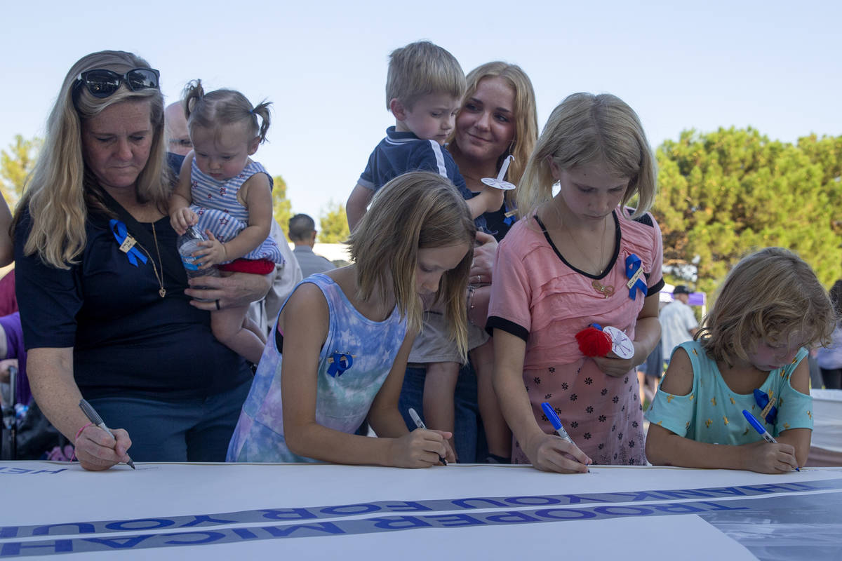 Family members hold Nevada Highway Patrol trooper Micah May's children Melody May, left, and Ra ...