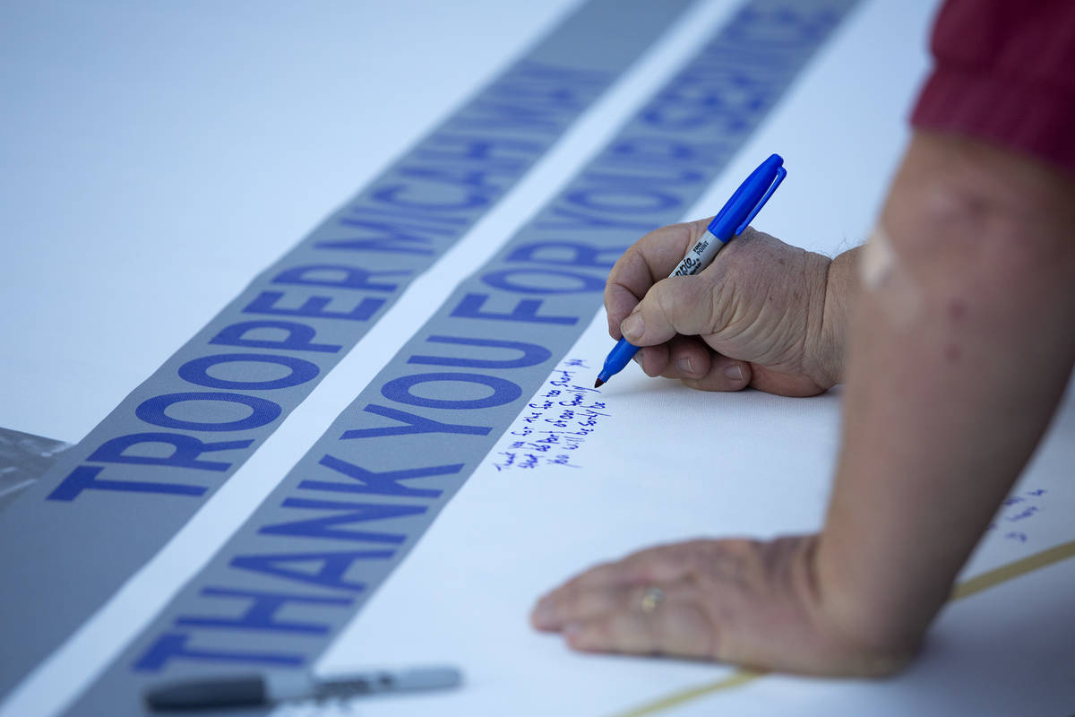 Family, friends and colleagues sign a banner for fallen Nevada Highway Patrol trooper Micah May ...