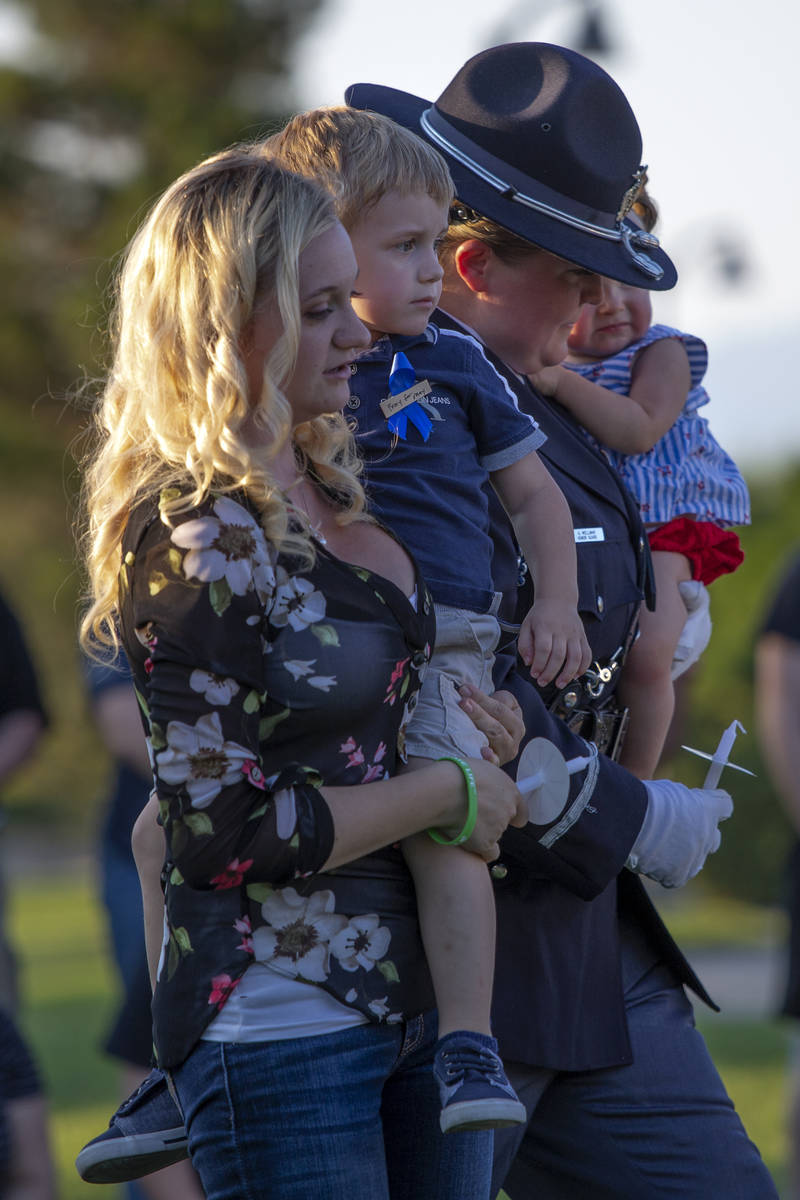 Joanna May holds her son Raylan May while a member of the Honor Guard brings her daughter Melod ...