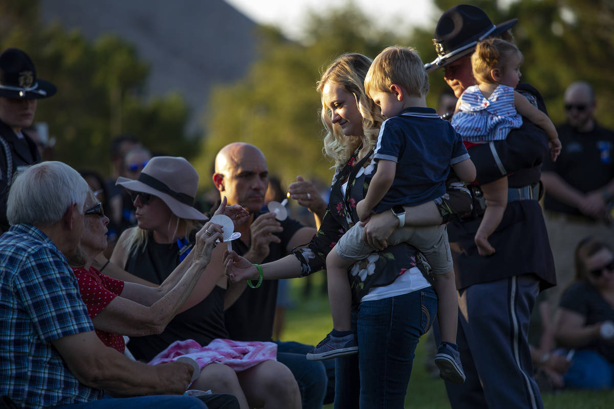 Joanna May, holding her son Raylan May, helps family members to light candles during a vigil fo ...