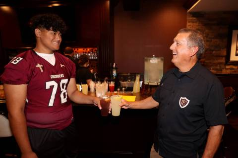 Faith Lutheran coach Mike Sanford and right tackle Vili Fetapai, 78, joke during Southern Nevad ...