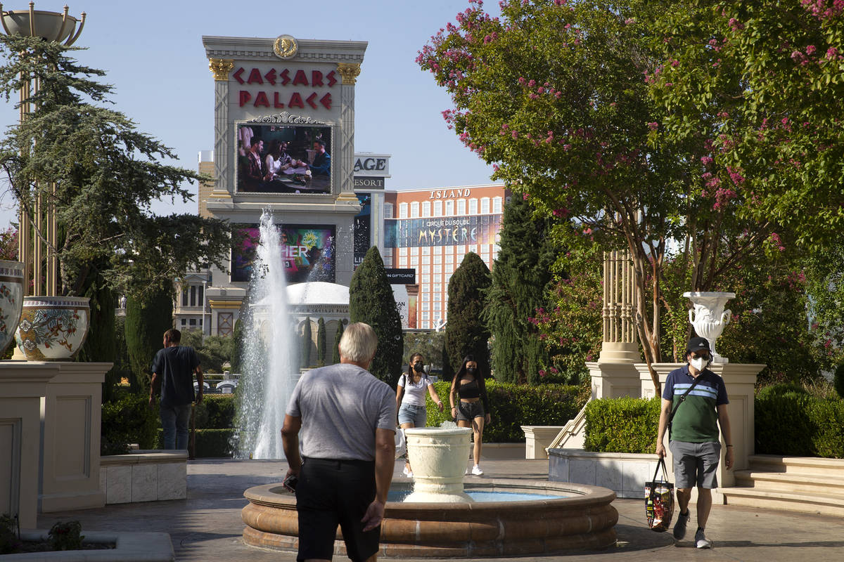 Visitors stroll on the Caesars Palace property on Wednesday, Aug. 4, 2021, on the Las Vegas Str ...