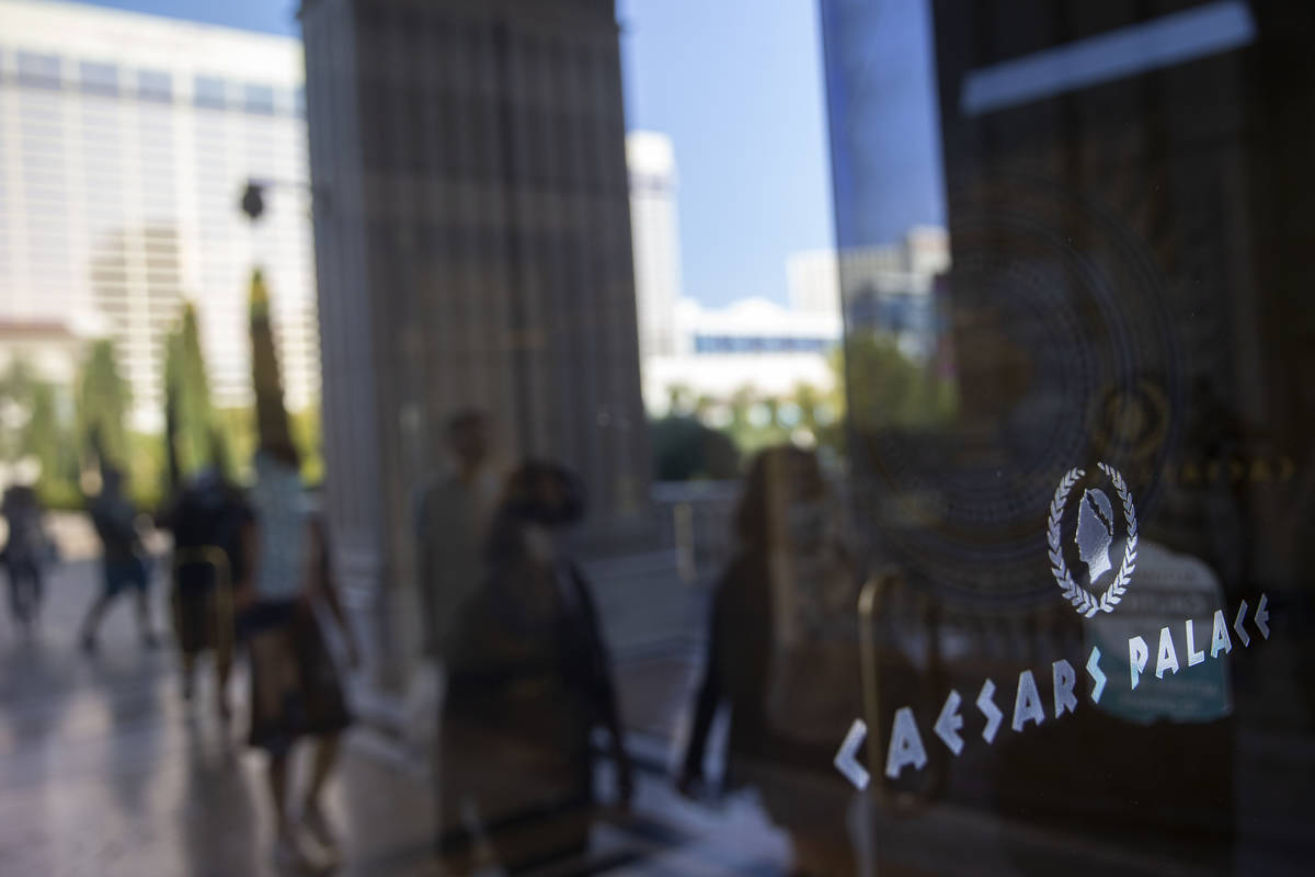 Visitors to the Las Vegas Strip are reflected in the door while entering Caesars Palace on Wedn ...