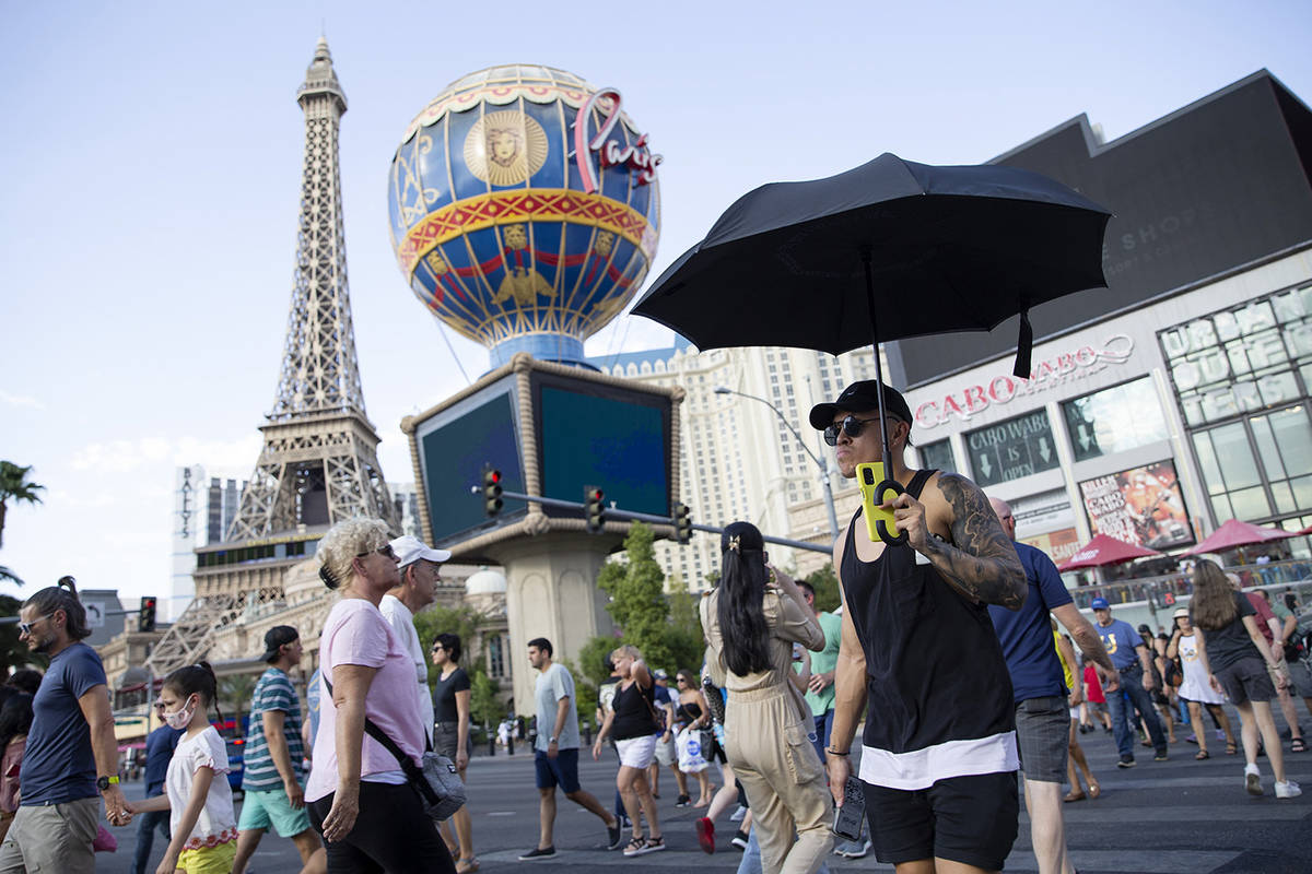 A visitor to the Las Vegas Strip uses an umbrella to shade himself from the sun on Wednesday, J ...