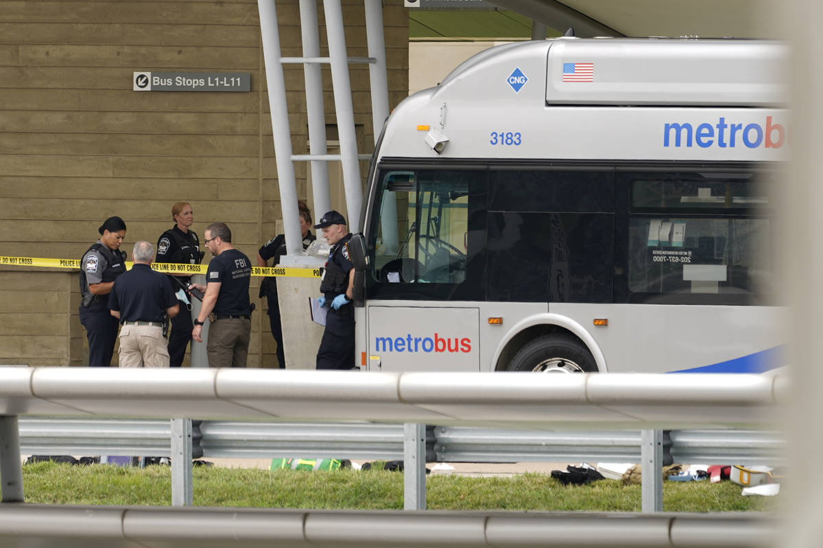 Police are looking at a scene and items are seen on the ground near a Metrobus outside the Pent ...